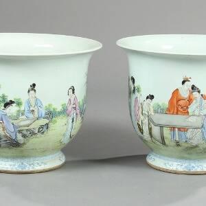 Et par kinesiske urtepotteskjulere af porcelæn i overglasur med figurscenerier. Signerede. 19.-20. årh. H. 36,5. Diam. 46. 2