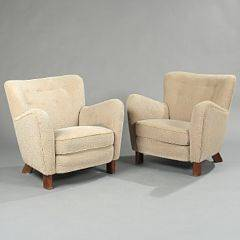 Fritz Hansen design Et par overpolstrede lænestole på ovale ben af mørkbejdset bøg, betrukket med lyst møbelstof. Udført hos Fritz Hansen. 2